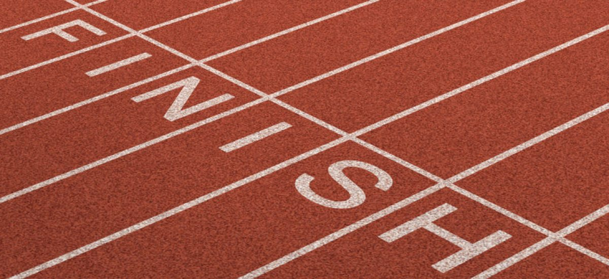 Finish Line as a business symbol of success in completing a planned strategy to acheive victory and reach the goals of financial freedom and wealth as a track and field background in dimensional perspective